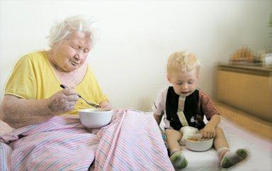 Pětadevadesátiletá stařenka s mladým příbuzným při společné snídani